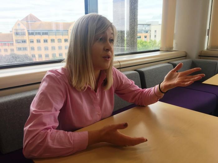 Lorna Edwards sitting in a desk talking.